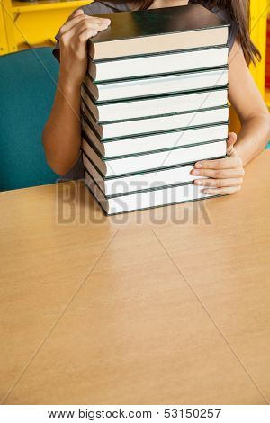 Cropped image of female student with stacked books at table in college library