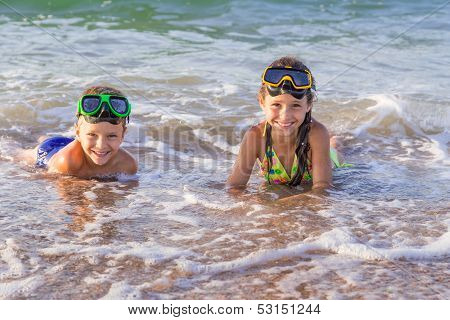 Two kids in diving masks on the sea