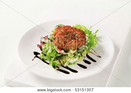 Rissole and vegetable garnish sprinkled tasty dressing