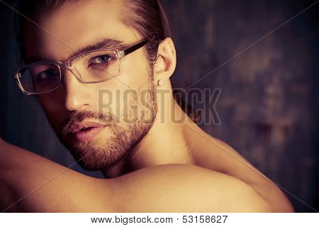 Sexual muscular nude man posing over dark background.