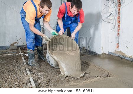 Two construction workers  pour out the mortar of cement from a bucket to pour the floor