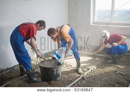 Three worker prepare the mixture and pouring the floor