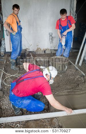 Three workers in construction room prepare the mixture and pouringl the floor