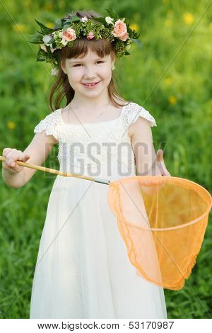 Little girl in white holds orange butterfly net on green meadow.