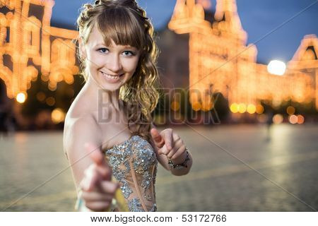 A smiling girl in a beautiful dress standing on a red square