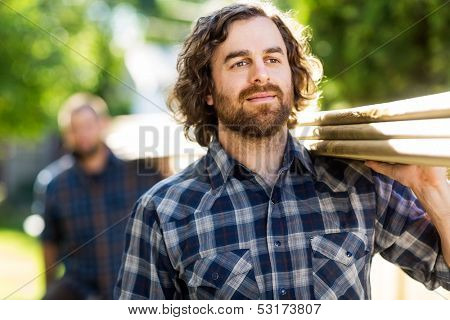 Mid adult carpenter carrying wooden planks with the help of coworker while looking away