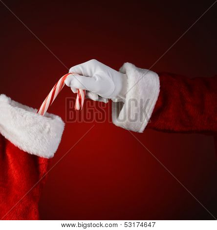 Santa placing a candy cane into a holiday stocking.  Square format on a red background.