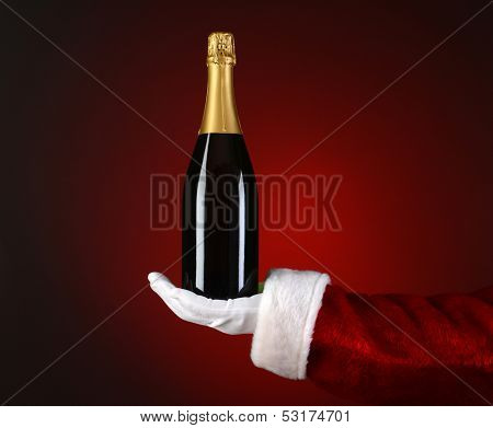 Closeup of Santa Claus holding a bottle of Champagne in the palm of his outstretched hand. Hand and arm only over a light to dark red spot background.