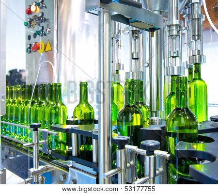 white wine in glass bottling machine at winery