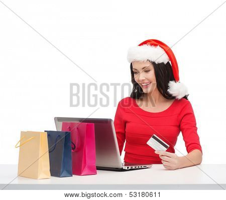 christmas, x-mas, online shopping concept - woman in santa helper hat with shoopping bags, laptop computer and credit card
