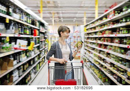Mulher às compras e escolhendo mercadorias no supermercado