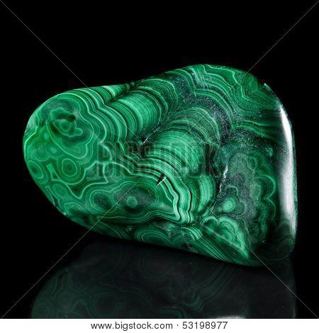 Polished malachite stone close up detail with reflection on black surface background