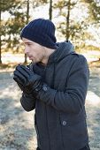 stock photo of shivering  - Young man in warm clothing shivering while having a walk in forest on a winter day - JPG
