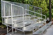 pic of bleachers  - A set of metal bleachers in an empty baseball field - JPG