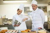 stock photo of cake stand  - Serious chef whisking while being watched by head chef in professional kitchen - JPG
