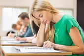 stock photo of classroom  - Side view of a group of young students writing notes in the classroom - JPG