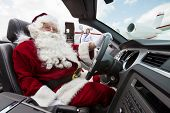 Portrait of Santa driving convertible with pilot and airhostess standing in background at airport te