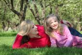 Mother Embraces Daughter Lying On Grass In Park