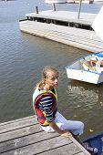 picture of gril  - A gril sitting on a yetti with her optimist sailing boat