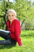 Beautiful Blonde Sits On Grass In Garden In Spring