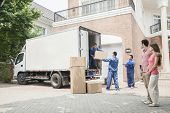 stock photo of life events  - Young couple watching movers move boxes from the moving van - JPG