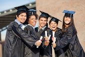 stock photo of graduation hat  - Portrait of happy students in graduation gowns showing diplomas on university campus - JPG