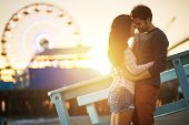 image of romantic love  - romantic couple kissing at sunset in fromt of santa monica ferris wheel - JPG