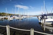 stock photo of marina  - Lots of sails boats at the boat marina harbor at the southern end of Seneca lake in Watkins Glen New York on a beautiful blue sky day in autumn - JPG