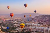 stock photo of balloon  - Hot air balloon flying over rock landscape at Cappadocia Turkey - JPG