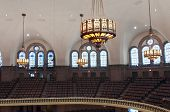 stock photo of church interior  - Interior of lutheran church on upper balcony showing seats lights and stained glass windows under vaulted ceilings - JPG