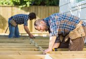 stock photo of carpenter  - Side view of mid adult carpenters working at construction site - JPG