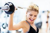 stock photo of lifted  - Woman in gym lifting weights - JPG