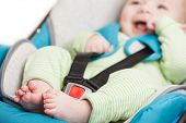 pic of car ride  - Little smiling baby child fastened with security belt in safety car seat - JPG
