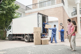 picture of moving van  - Young couple watching movers move boxes from the moving van - JPG
