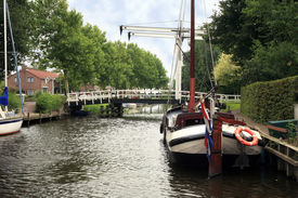 picture of flatboat  - View on typical canal with different boats and white drawbridge - JPG