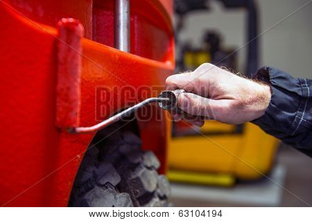 Mechanic putting a fresh paint coat on a used forklift during a maintenance and uphaul service