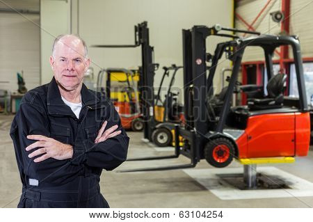 man standing in front of a few forklifts in a maintenance service area.