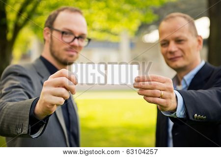 Two smart casually dressed businessmen presenting their business cards to a new network