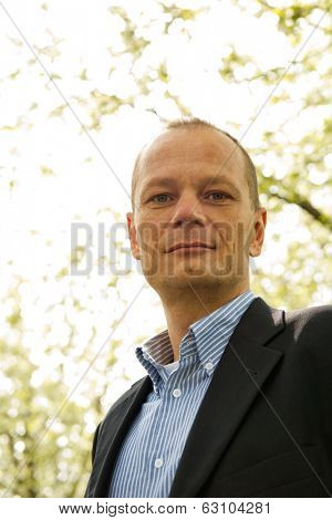Backlit portrait of a friendly business man. A happy average guy, dressed smart casual, seen from a low point of view, looking ito the camera