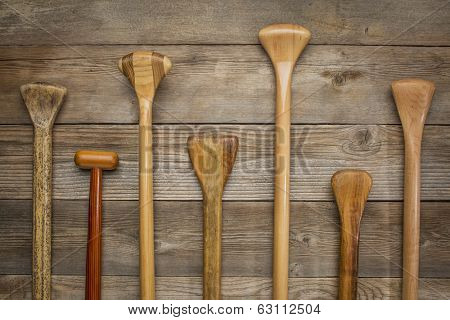 grips and shafts of old wooden canoe paddles against weathered wood background