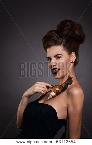 Sexy Woman With Snail In Black Dress. Fashion. Gothic