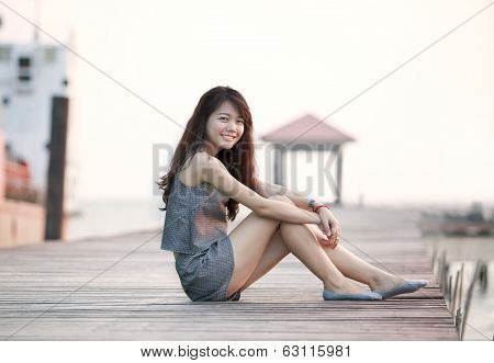 Beautiful Asian Woman Sitting On Wood Pier With Relaxing Emotion And Smiling To Camera Use For Attra