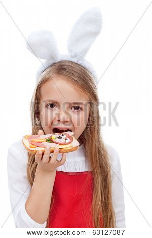 Little girl with bunny ears biting into a sandwich decorated with rabbit shape - isolated