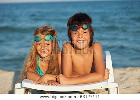Kids laying on beach chair wearing swimming goggles in the bright sunshine