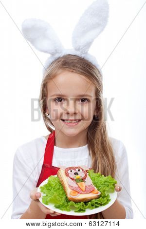 Happy bunny chef presenting her masterpiece - a rabbit shaped sandwich, isolated