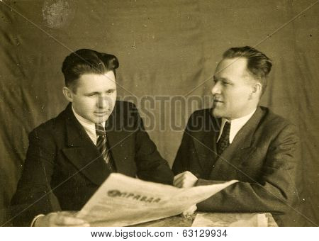 LODZ, POLAND, CIRCA 1940's: Vintage photo of two men, one of them reading a soviet newspaper