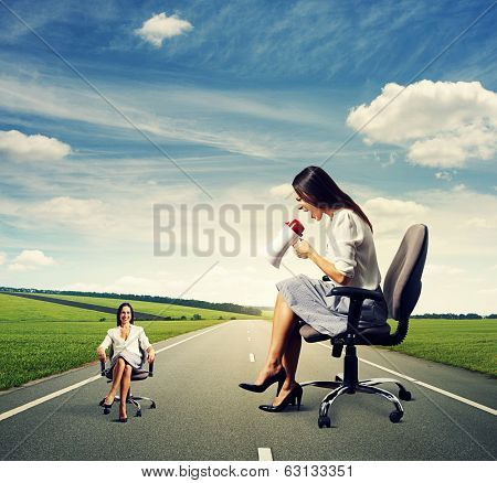 angry woman and calm woman on the chair over dark background
