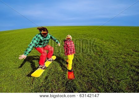 Young Couple In Sport Wear Snowboarding On The Grass In The Greenfield