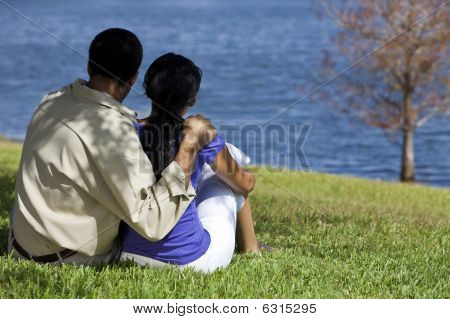 Rear View Of African American Couple Sitting By Lake