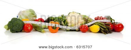 A Row Of Vegetables And A Tape Measure On White
